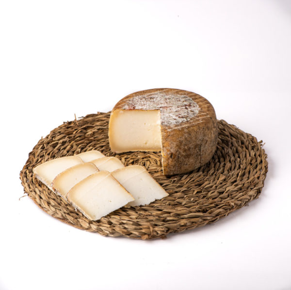 Queso de cabra O Pepiño, pieza cortada en lonchas y lista para degustar en tabla de mimbre
