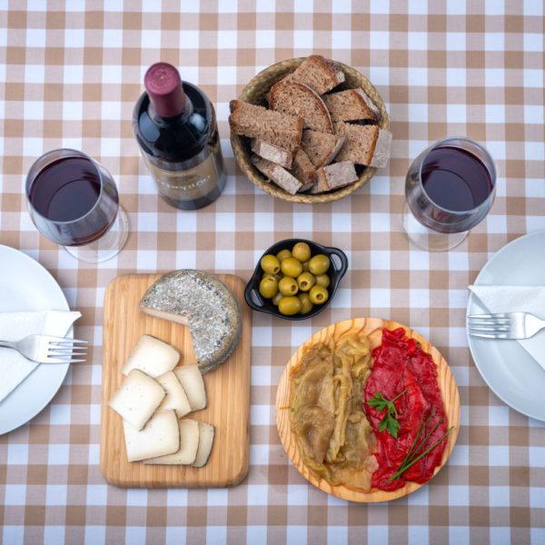 Productos en mesa del pack O Pepiño con queso gallego, botes de pimientos Oímbra y mencía